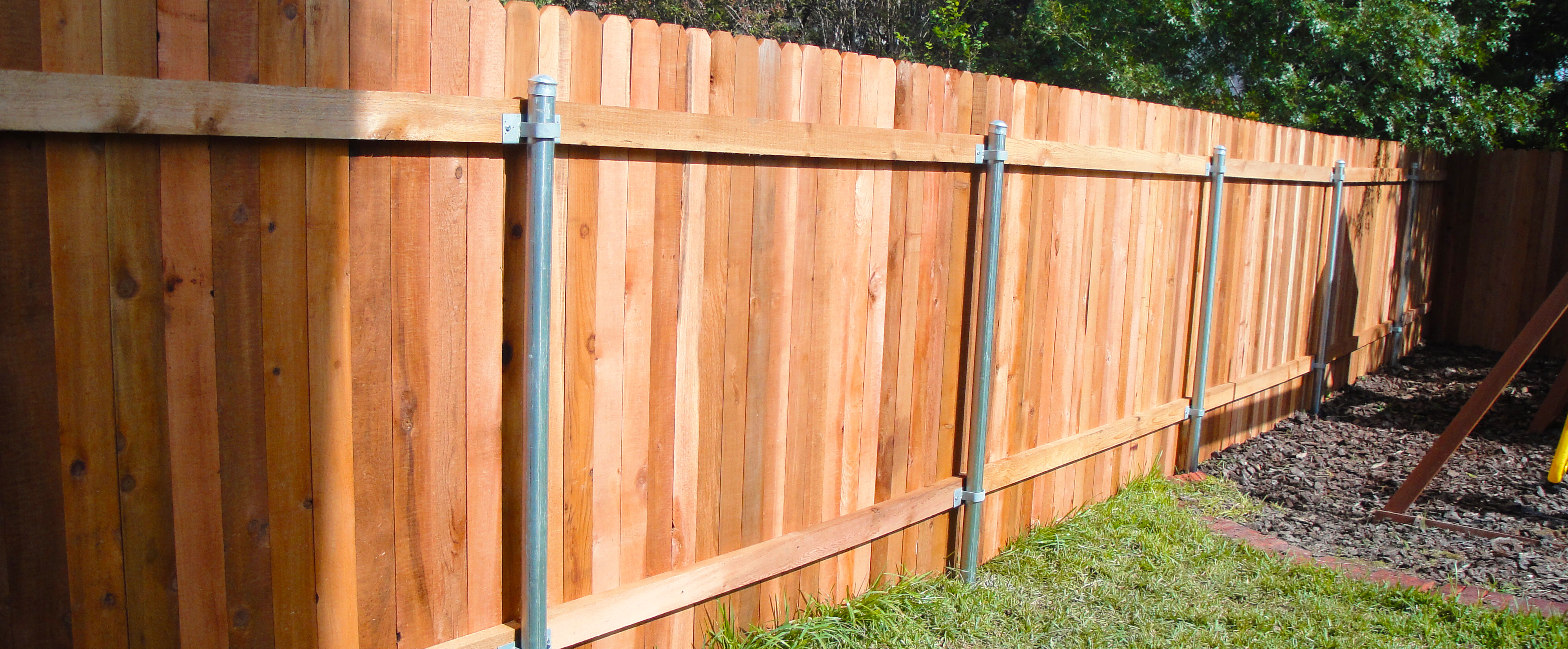 Wooden backyard fence with steel posts